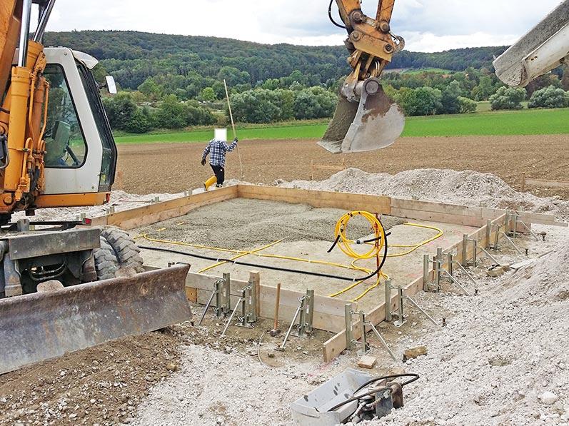 Lhotzky und Partner Bauwerksmonitoring: Vorsichtiges Übergießen des Messsystemschlauchs mit Beton und Herstellung der Fundamentplatte